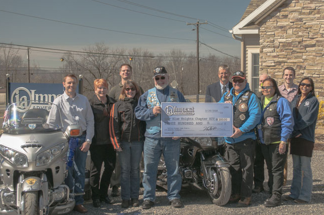 "Members of the Blue Knights Motorcycle Club meet with employees of Impact Advertising to receive a donation towards the clubs annual Special Olympics ""Making Dreams Come True"" charity ride fundraiser."